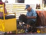 Cireur de chaussures sur la Plaza de Armas de Santiago Schoenenpoetser op de Plaza de Armas in Santiago